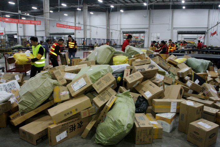 """Employees of Cainiao Network Technology Co. Ltd.'s logistics park in Jinhua, Zhejiang province, sort through packages during China's """"Double Eleven"""" holiday, on Nov. 11, 2016. Photo: VCG"""