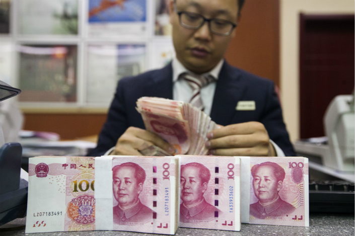 A bank employee counts cash in Taiyuan, Shanxi province on April 13. Photo: VCG