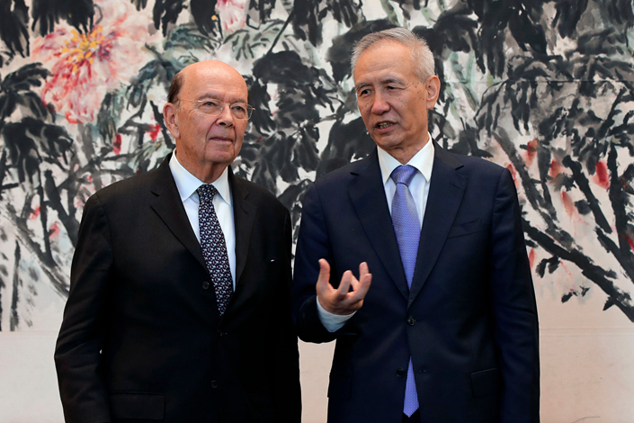 Chinese Vice Premier Liu He (right) chats with U.S. Commerce Secretary Wilbur Ross during a photograph session after their meeting at the Diaoyutai State Guesthouse in Beijing on June 3. Photo: VCG