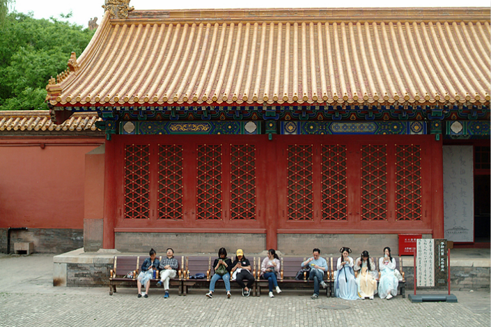 Tourists, including some who dressed up in traditional Chinese costumes, take a break beside an art exhibition hall in the Forbidden City in Beijing on May 5. Photo: Wu Gang/Caixin