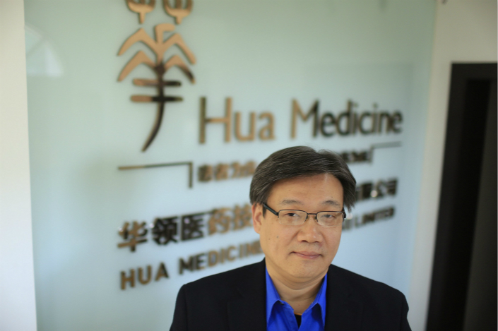 Li Chen, co-founder and CEO of Hua Medicine, poses for a photograph in front of a company logo at his office in Shanghai in February 2015. Photo: VCG