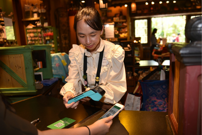 A cashier at a Hong Kong Disneyland gift shop scans a customer's WeChat payment information on May 24. Photo: VCG
