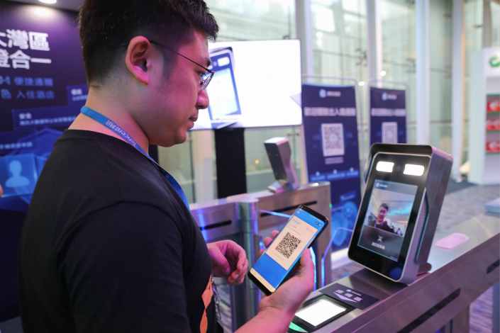 A Tencent employee demonstrates how the e-version of identities may be used in practice at the border between Hong Kong and the Chinese mainland. Photo: VCG