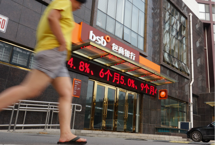 A pedestrian walks in front of a Baoshang Bank branch in Beijing in August 2013. Photo: IC