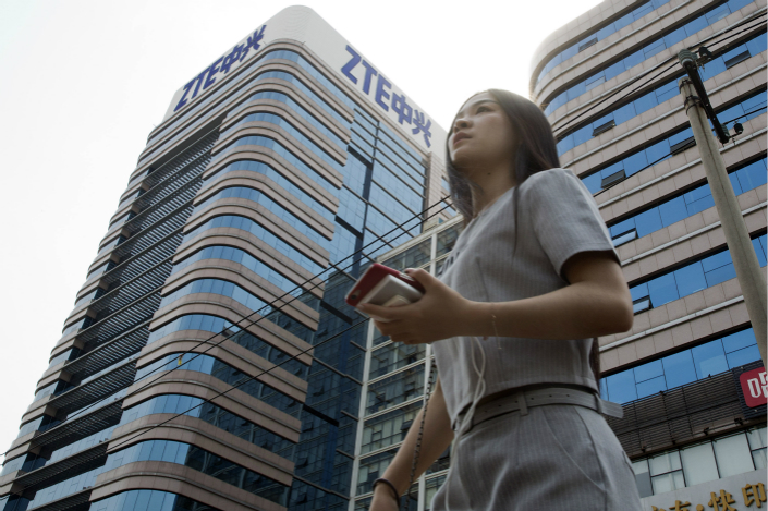A pedestrian passes a ZTE building in Beijing on May 8. Photo: IC