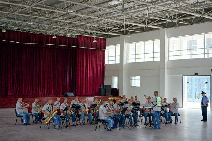 A prisoners' orchestra rehearses in the music hall at Chuanbei Prison under the watch of a guard. The band practices five hours a day in order to be ready to perform on short notice. Photo: Liang Yingfei