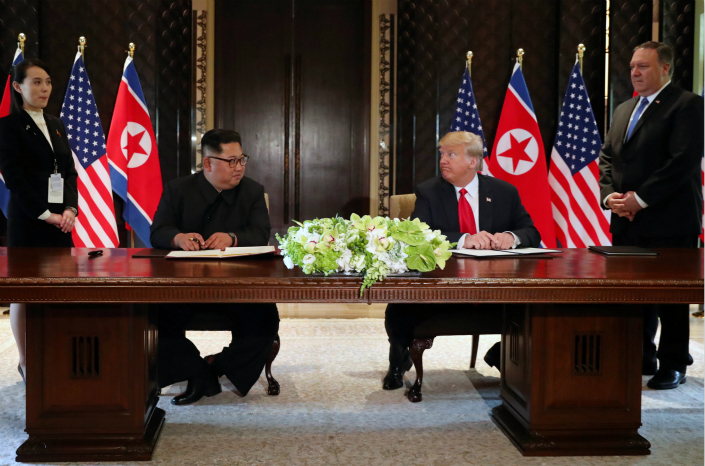 North Korean leader Kim Jong Un and U.S. President Donald Trump prepare to sign documents that acknowledge the progress of their talks after their summit at the Capella Hotel in Singapore on Tuesday. Photo: VCG