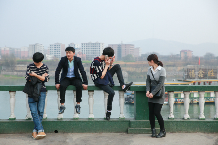 Young people take a break near the river in Leiyang, Hunan province, in February 2015. Photo: VCG