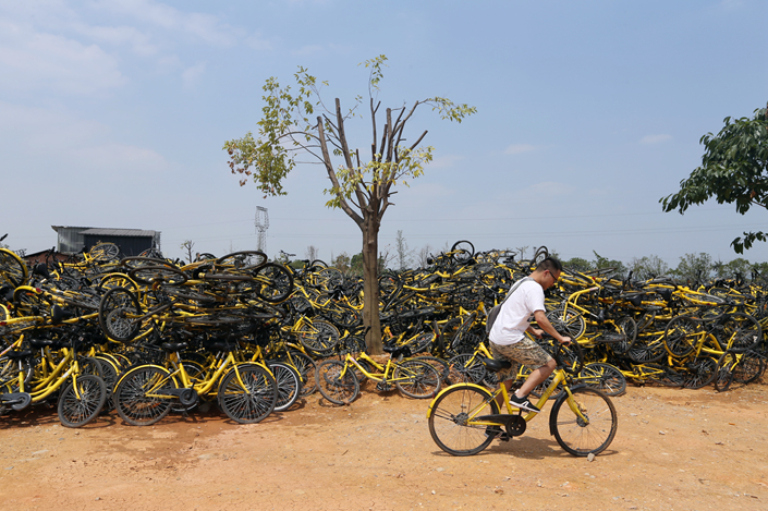 A man cycles past piles of Ofo shared bikes which are stored near a Chengdu subway station on June 6. Ofo says they are only kept there temporarily while they wait for maintenance. Photo: VCG