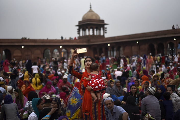 A woman holds her child on June 6 as she records on her mobile phone a gathering in the compound of historical Jama Masjid in New Delhi on the 21st day of Ramadan. Photo: IC