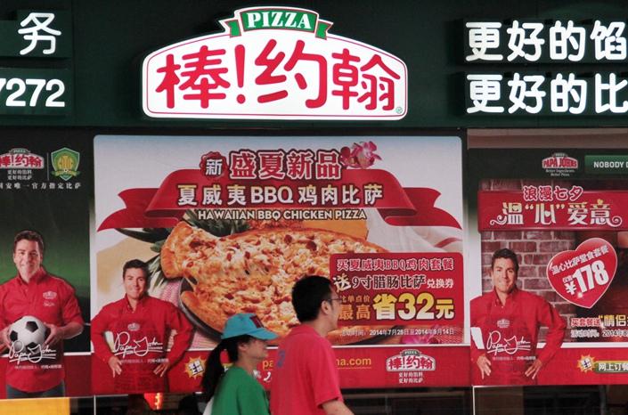 Pedestrians walk past a Papa John's advertisement in Beijing in August 2014. Photo: VCG