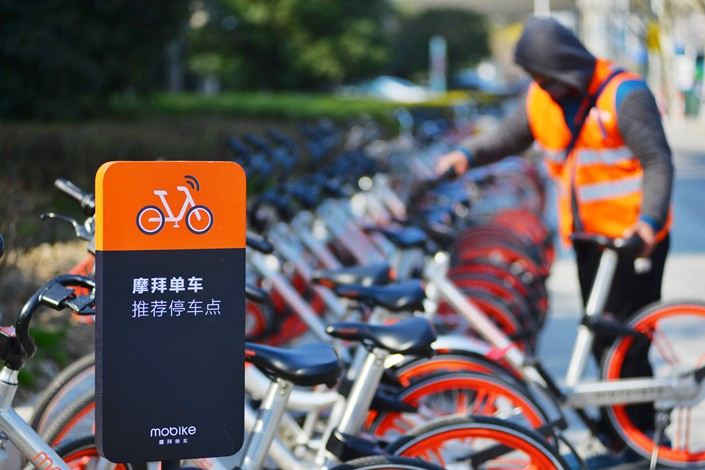 A worker lines up Mobikes at a roadsite parking site in Shanghai on March 2, 2017. Photo: IC