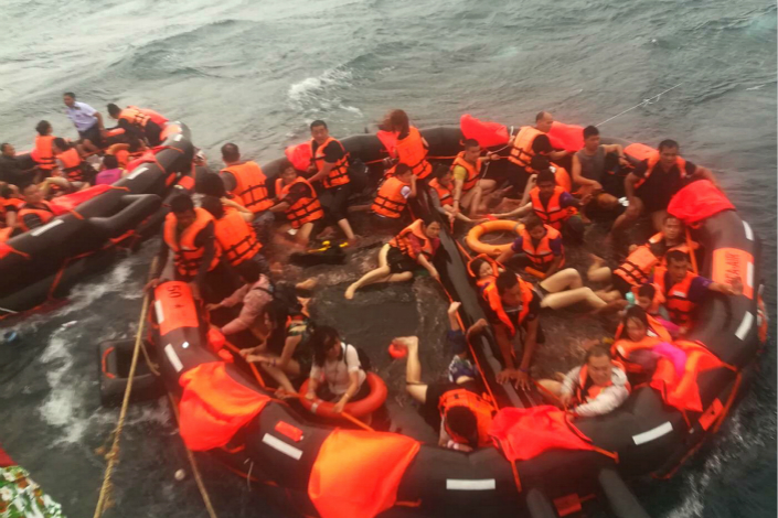 Rescued tourists from a capsized tourist boat are brought aboard a fishing vessel in the seas off Phuket, Thailand, on Thursday. Photo: IC