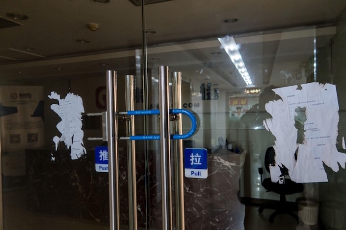 The door to the office of a P2P lending site in Shanghai is locked in February. Photo: VCG