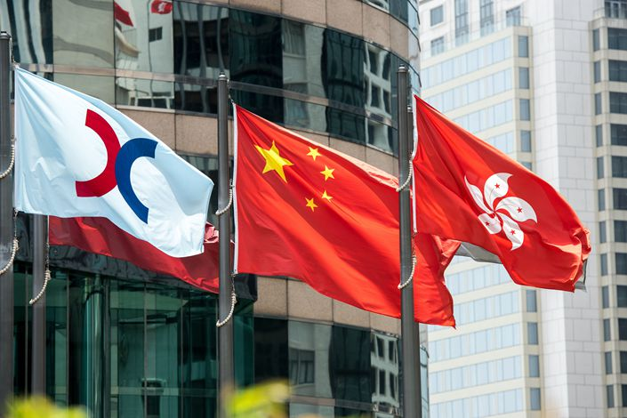 The flag of Hong Kong Exchanges and Clearing Ltd. (HKEx) (left) flies alongside the flags of China (center) and Hong Kong outside the HKEx building in the city's Central district in August 2016. Photo: VCG