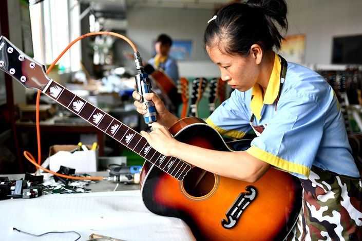 Workers inspect guitars at a Zhengan country industrial park in Zunyi city, Guizhou province, on July 10. Photo: VCG