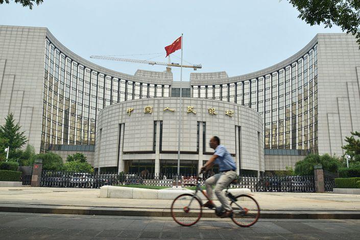 A cyclist bikes past the People's Bank of China in Beijing on July 5. Photo: VCG
