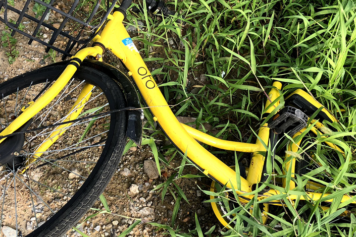 A damaged Ofo bike lies on a roadside in eastern Beijing on Monday. Photo: Wu Gang/Caixin