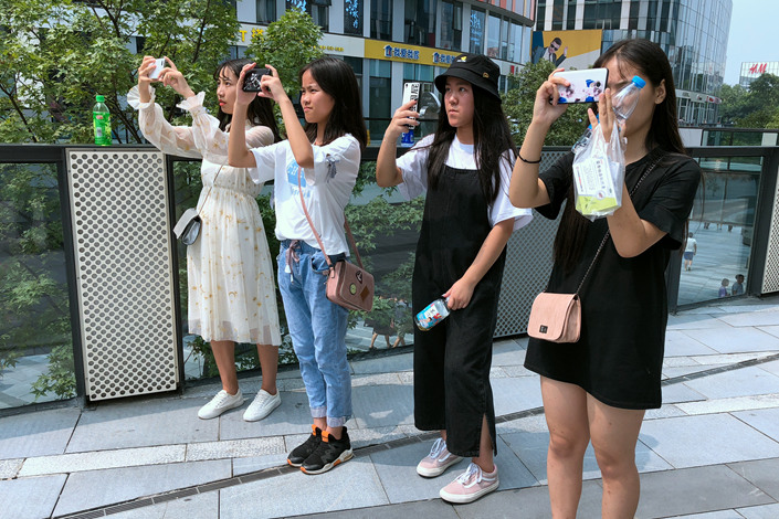 Teenagers take picture of a screen showing an entertainer in downtown Beijing's Sanlitun area on Thursday. Photo: Wu Gang/Caixin