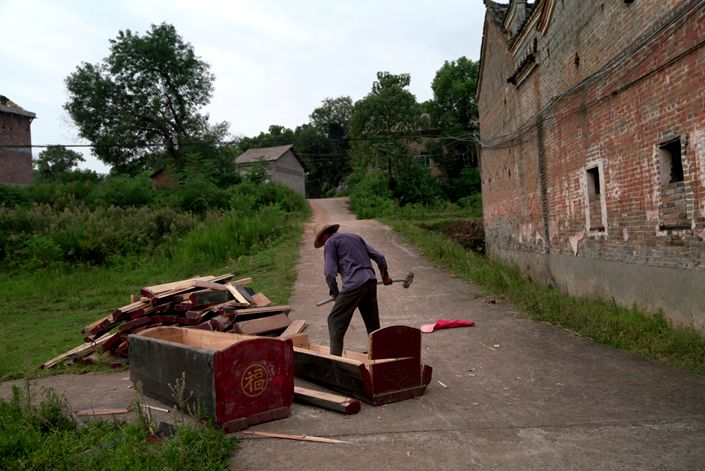 Workers smash coffins in Nanling, Maojia village, in Jiangxi province on Thursday. Photo: Liang Yingfei/Caixin