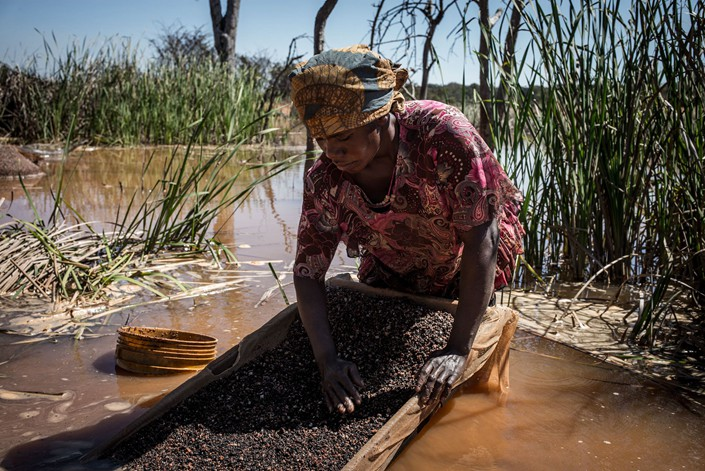 A woman pans for cobalt in May 2015 near a mine in the Congo. Photo: VCG
