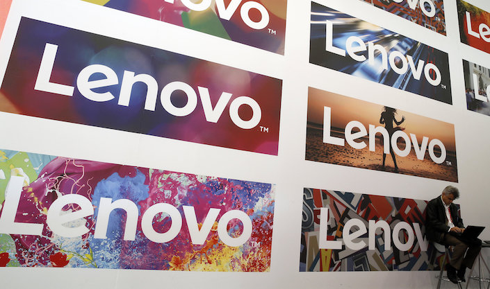 A man uses his laptop next to Lenovo's logos during the Mobile World Congress in Barcelona, Spain February 25, 2016.  Photo: VCG