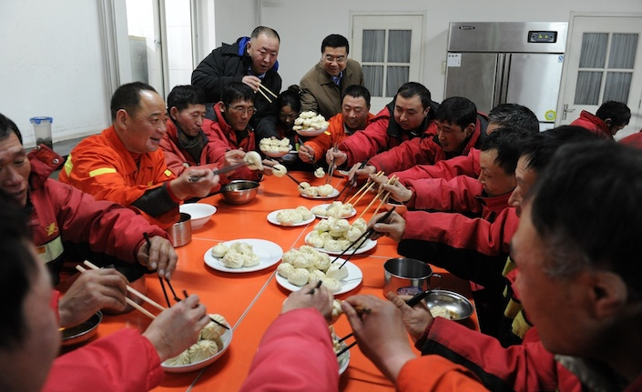 Sanitation workers are treated to a meal at a Qing-Feng dumpling restaurant in Beijing on Jan. 31, 2014. Photo: VCG