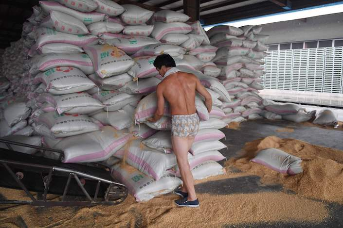 A worker loads sacks of animal feed made from soybeans at the Hopefull Grain and Oil Group in Sanhe, in China's Hebei province, on July 19, 2018. Photo: VCG