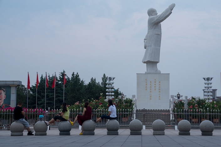 Visitors take a break at the Dongfang Hong Square at the center of Nanjie village, where a statute of Mao Zedong is visibly seen. Photo: Chen Liang/Caixin