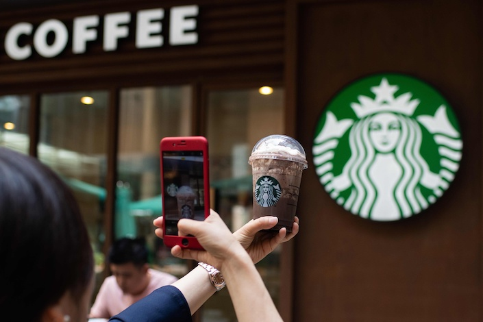 A woman takes a picture of her beverage at a Starbucks coffee shop in Beijing, on May 25. Photo: VCG