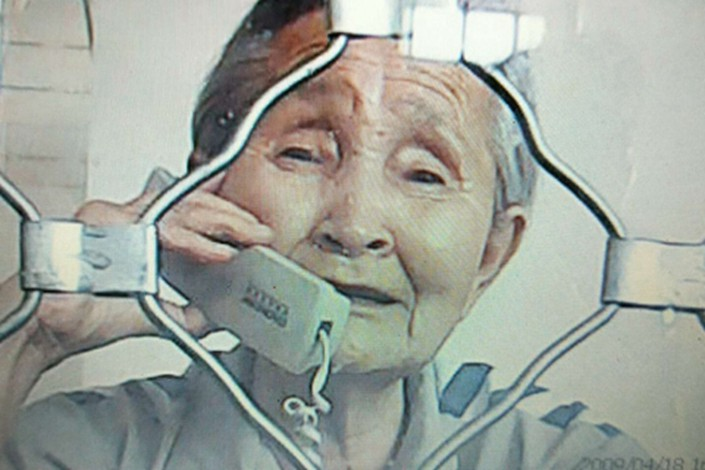Li Shuxian speaks on the phone during a visit by her daughter Guan Guixia in June. Photo: Li's family