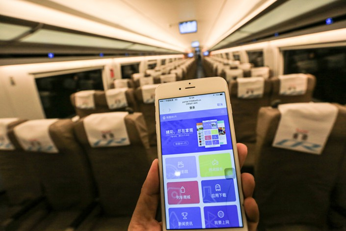 A passenger demonstrates the Wi-Fi connection on a Fuxing bullet train on Dec. 30. Photo: VCG