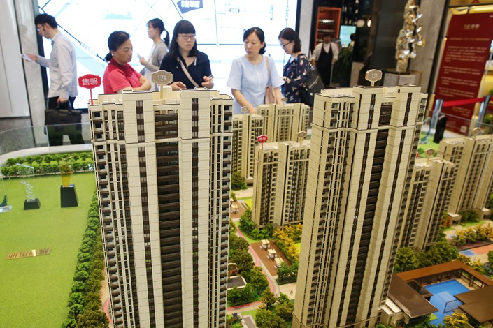 Potential buyers look at a model of an apartment block in Nantong, Jiangsu province on June 14. Photo: VCG