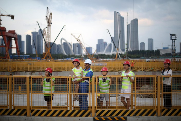 Construction workers in Nanjing, Jiangsu province, show children a work site on Saturday. Photo: VCG