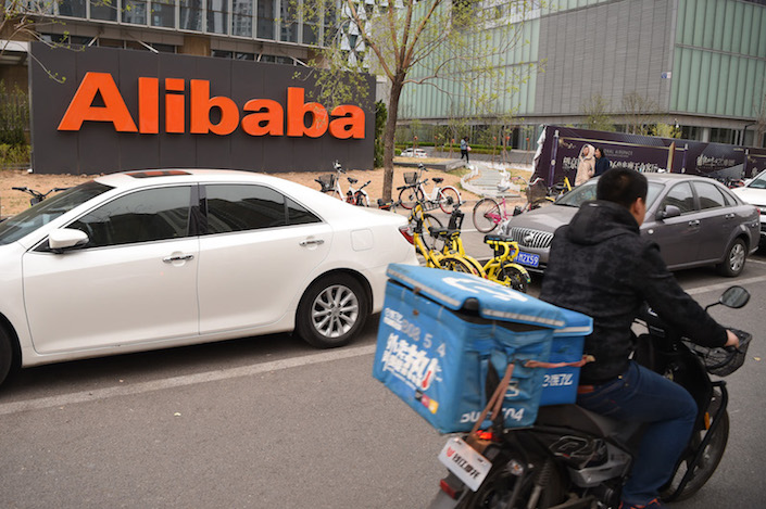 An Ele.me delivery man drives past Alibaba's office in Hangzhou. Photo: VCG