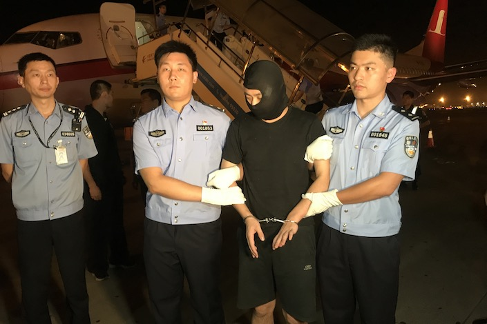 Zhu Yidong, his face obscured by a black mask, is escorted by policy officers at the Shanghai Pudong airport Aug. 29. Photo: VCG