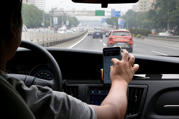 A Didi driver checks his phone while on the road in Beijing on Aug. 28. Photo: VCG