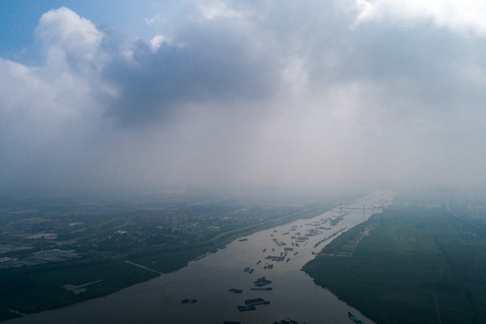 Some 800 boats, many loaded with sand, wait to pass a lock on the Bengbu section of the Huaihe River to further sail into the Shaying River, on Aug. 5. The congestion is caused by limited capacity at the facility and an official crackdown on sand excavation in Henan and Anhui provinces, which the river flows through. Photo: Chen Liang/Caixin