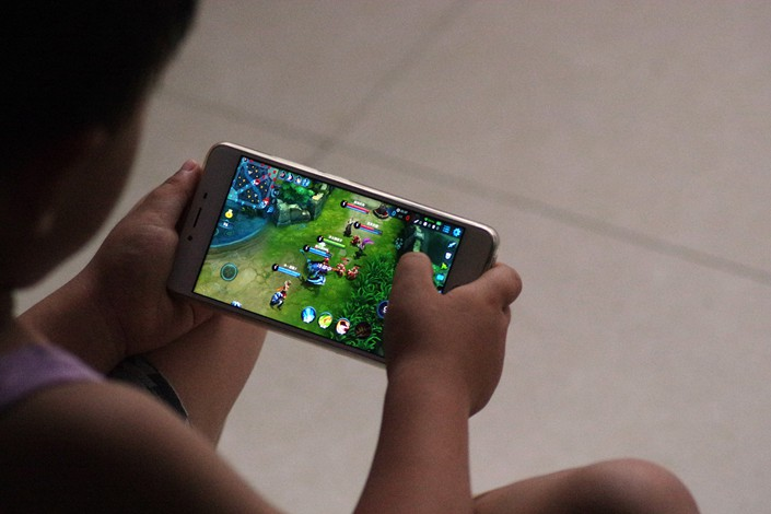 """A child plays the video game """"Honour of Kings"""" on his mobile phone in July 2017 in Dezhou, Shandong province. Photo: VCG"""