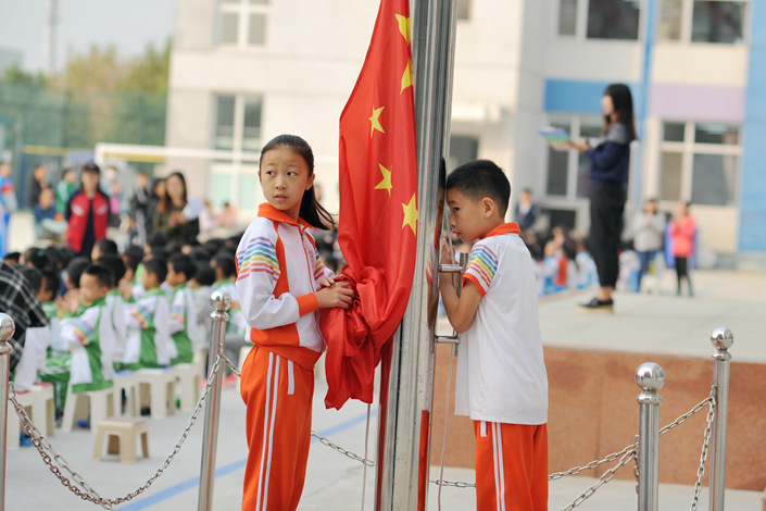 Two students prepare to raise a flag at a school in eastern Beijing on Sept. 30. Photo: Wu Gang/Caixin