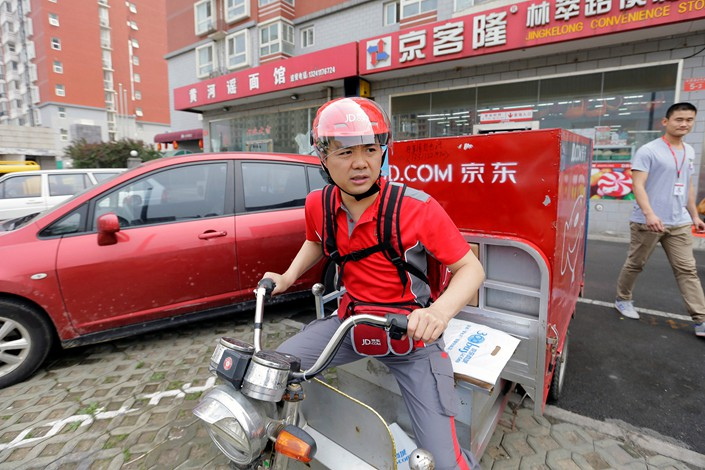 Richard Liu, founder and CEO of JD.com Inc., prepares to deliver goods for customers in Beijing to celebrate the anniversary of the founding of the company, in June 2014. Photo: VCG