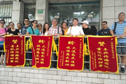 Fuxing Group investors display banners calling for the conviction of the wealth management group's leaders, outside Shanghai police offices on Aug. 31. Photo: Fuxing investors