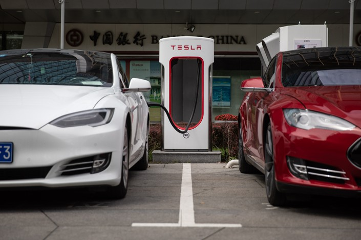 Electric cars top up their batteries at a charging station in front of Tesla's China headquarters in Beijing on July 25. Photo: IC