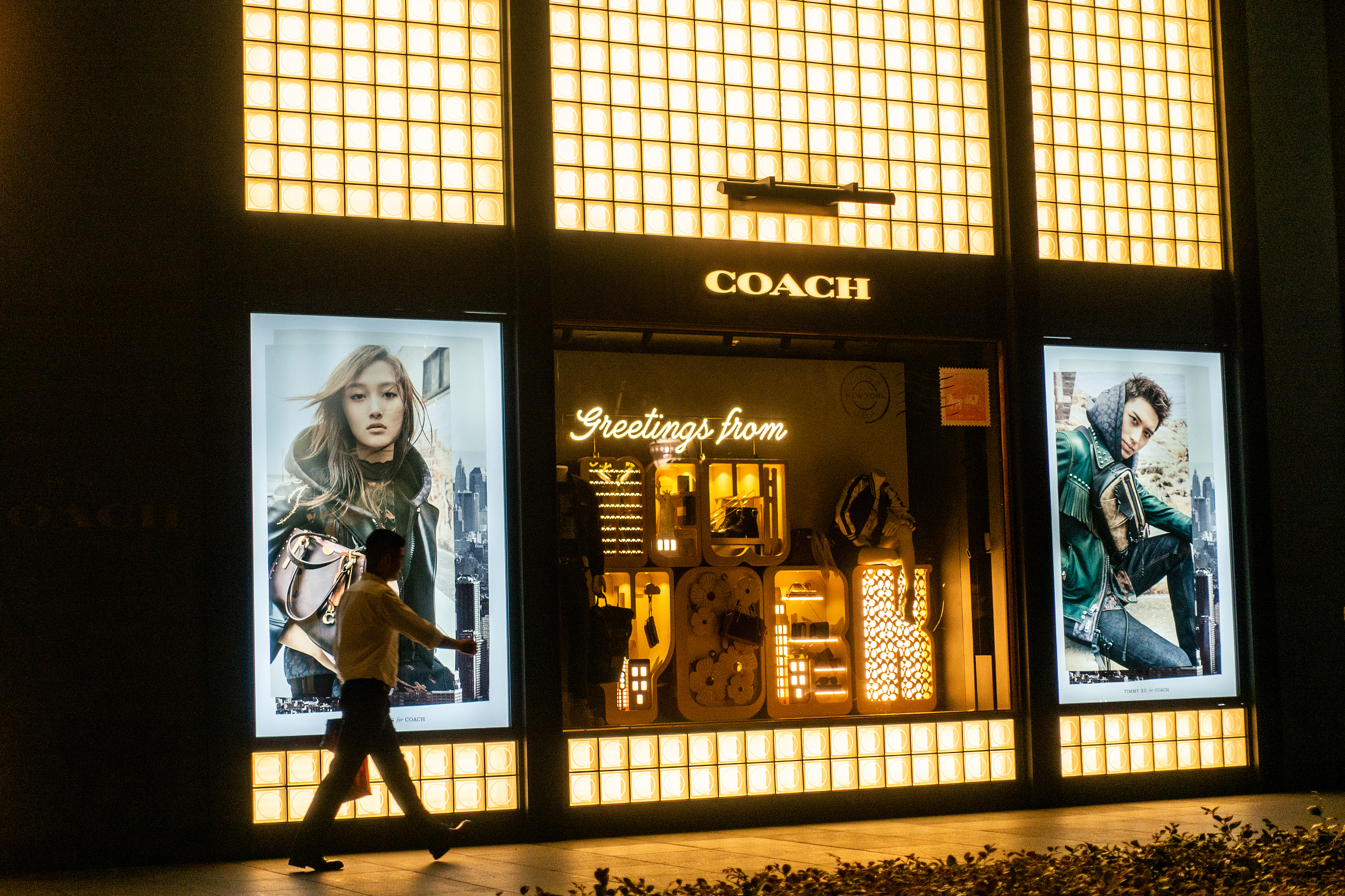 Consumer walks by Shanghai store operated U.S. luxury goods seller Coach. Photo: VCG