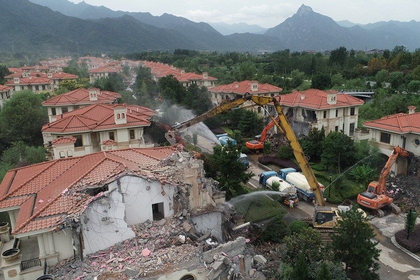 Construction vehicles accompanied by tanker trucks spraying water dismantle villas in Xi'an, Northwest China's Shaanxi province. The local government said the villas had been built illegally and had caused damage to the environment. On Thursday, more than 100 vehicles were deployed to demolish the 45 homes in the complex, called Qunxian Villa. The complex was one of 15 that the Xi'an government has condemned. Photo: VCG_Tearing Down the House
