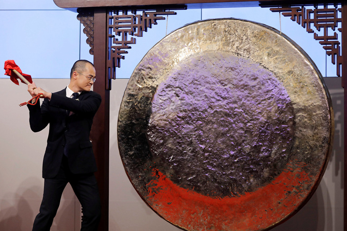 Wang Xing, chief executive officer of China's Meituan Dianping, strikes the gong to mark the company's trading debut on the Hong Kong stock exchange on Thursday. Photo: VCG