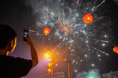 A villager photographs fireworks on the night of the Mid-Autumn Festival. Photo: VCG