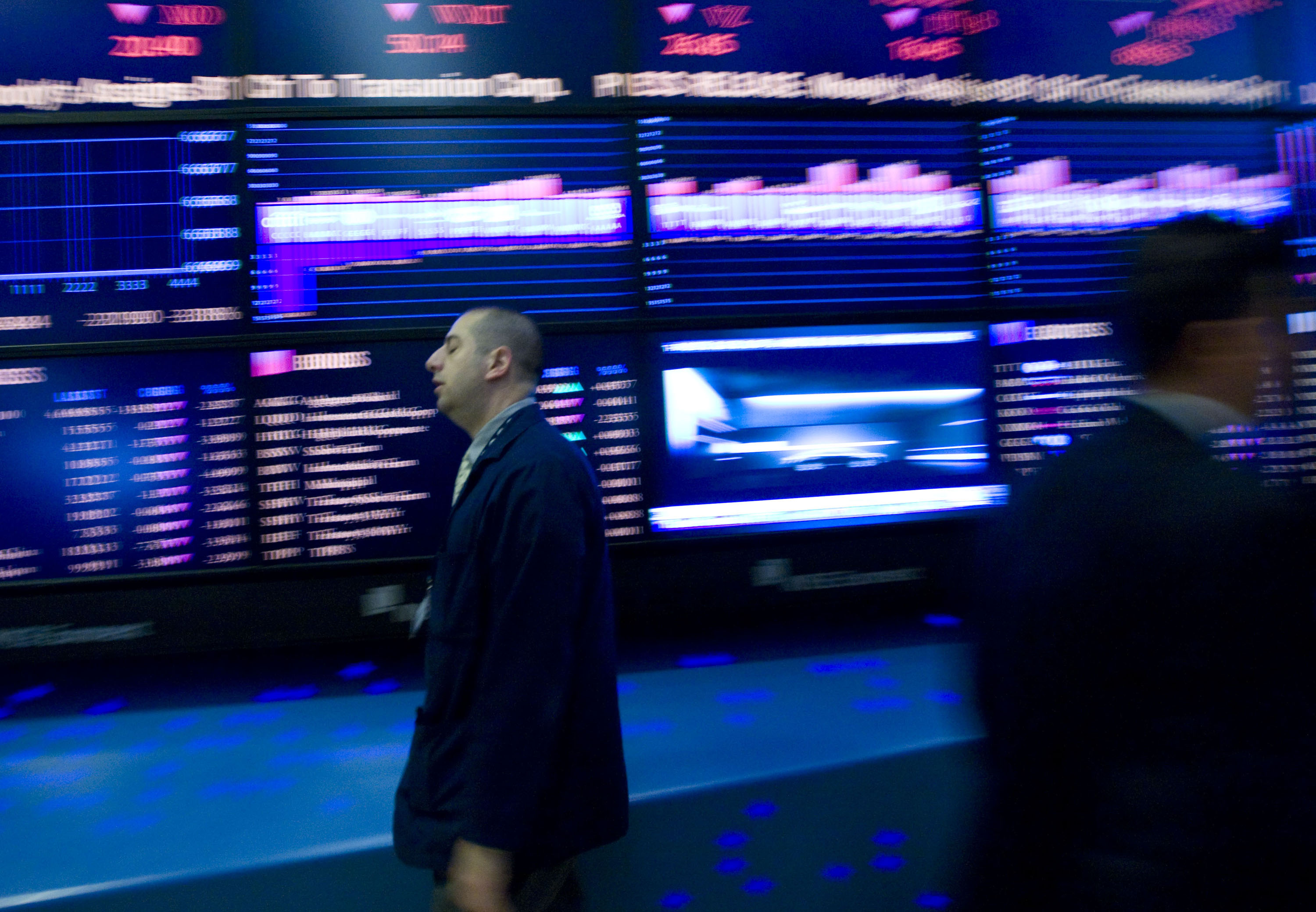 A trader walks past the board while working on the floor of the New York Stock Exchange in New York. Photo: Bloomberg