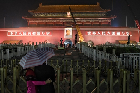 A couple watch the changing of the Mao Zedong portrait at Tiananmen on Thursday night. Photo: VCG