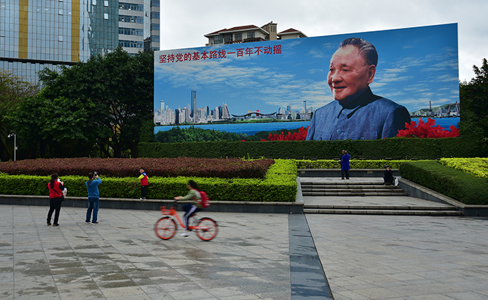 People cycle past former Chinese leader Deng Xiaoping in Deng Xiaoping Portrait Square in the southern city of Shenzhen on Feb. 23. Photo: VCG